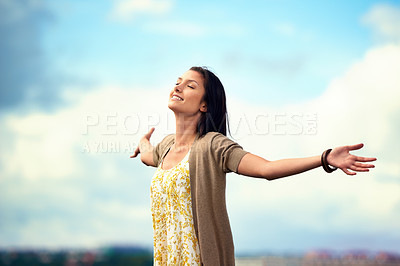 Buy stock photo Attractive young woman feeling relaxed and carefree on a rooftop