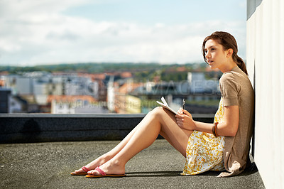 Buy stock photo Young woman journaling while seated on a rooftop