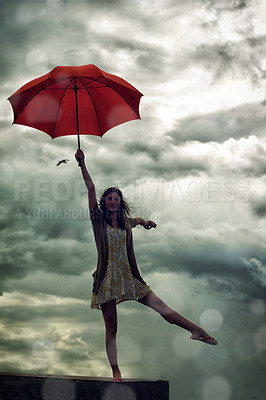 Buy stock photo Cute young woman holding an umbrella while standing in a ballet pose on a rooftop