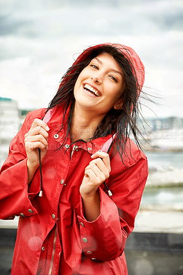 Buy stock photo Pretty young woman smiling while wearing a red raincoat - portrait