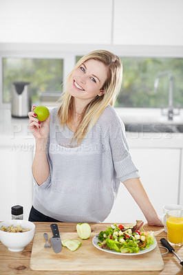 Buy stock photo Happy young woman making healthy food choices at home