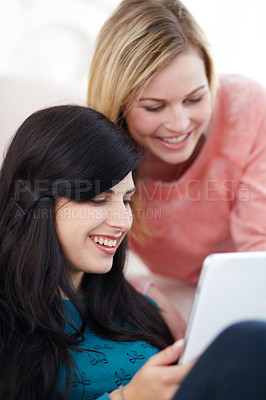 Buy stock photo Smiling young women using a digital tablet together
