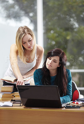 Buy stock photo Young female students studying together and using a laptop