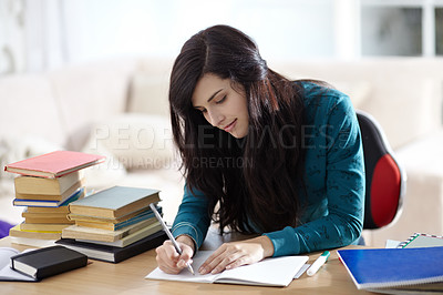 Buy stock photo Attractive young student sitting at a desk and studying