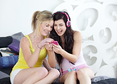 Buy stock photo Two young female friends listening to music on a smartphone together