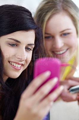 Buy stock photo Two young female friends listening to music on a mp3 player together