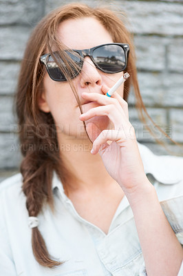 Buy stock photo Trendy young hipster girl smoking a cigarette