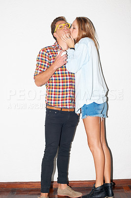 Buy stock photo Young hipster couple kissing and standing against a white wall