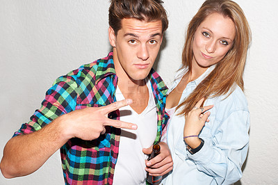 Buy stock photo Young hipster couple giving the V-sign while standing together