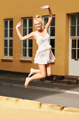 Buy stock photo A gorgeous blonde woman jumping in the air