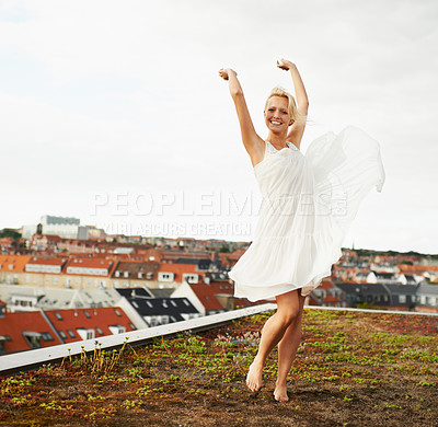Buy stock photo Beautiful young woman dancing on a rooftop with a city in the background