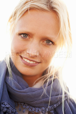 Buy stock photo A beautiful young woman smiling against bright sunlight