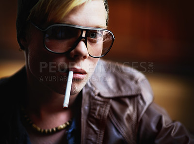 Buy stock photo Young guy in urban attire with a cigarette hanging from his lips