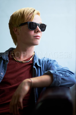 Buy stock photo Attractive young guy wearing hipster shades and looking away