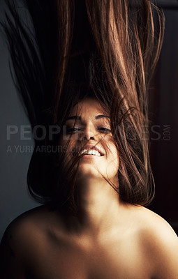Buy stock photo Gorgeous latina woman flinging her hair against a dark background