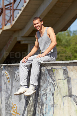 Buy stock photo A young man in sportswear sitting on a graffiti-filled wall