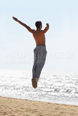 Buy stock photo An athletic young man jumping into the air at the beach