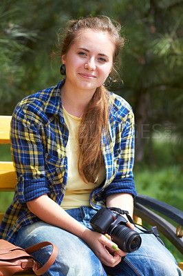 Buy stock photo A gorgeous young woman sitting in a park holding her camera