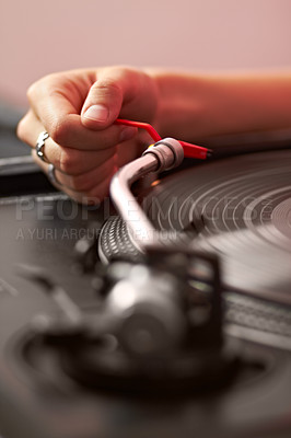 Buy stock photo Closeup of a dj's hand putting on a record