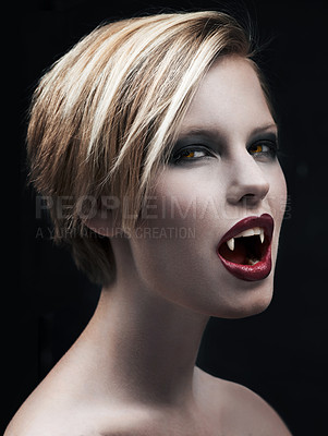 Buy stock photo A seductive female vampire baring her fangs and looking at you