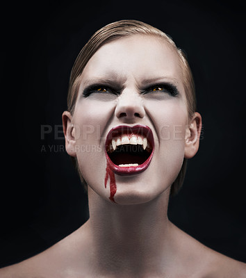 Buy stock photo A provocative female vampire with blood running down her chin