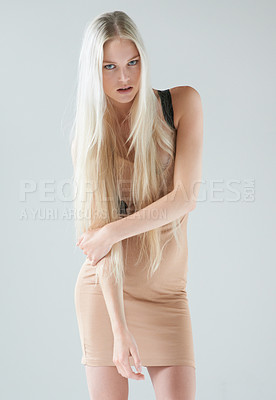Buy stock photo Portrait of an attractive young female wearing a dress and holding her arm