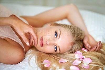 Buy stock photo Portrait of an attractive woman lying on her bed with rose petals in her hair