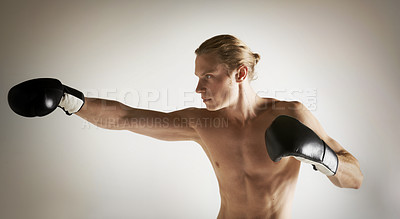 Buy stock photo A handsome young male boxing shirtless