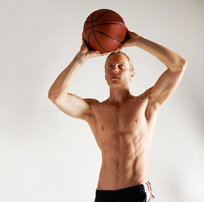 Buy stock photo Studio shot of a handsome young man playing basketball