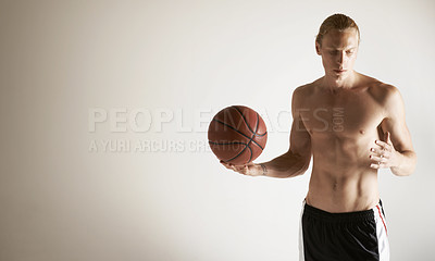 Buy stock photo A handsome young man holding a basketball
