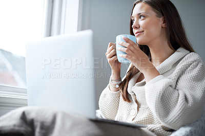 Buy stock photo Attractive young brunette sipping coffee while sitting at home in front of her laptop