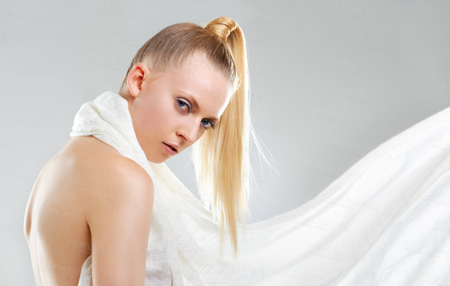 Buy stock photo Portrait of an attractive young woman weating a white scarf against a gray background