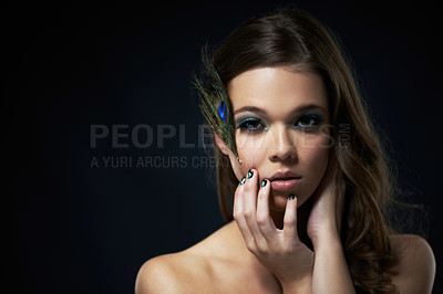 Buy stock photo Shot of a young brunette with peacock-themed makeup against a dark background