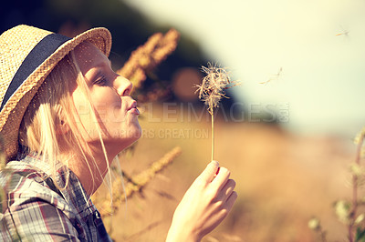 Buy stock photo Beautiful young woman wearing a straw fedora and blowing at a dandelion
