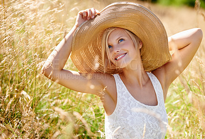 Buy stock photo Gorgeous young woman wearing a straw hat and stretching in a field