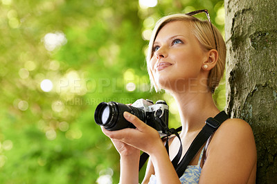 Buy stock photo Cute young photographer holding her camera and leaning against a tree