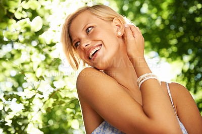 Buy stock photo Cute young blonde woman toying with her hair while standing in a forest