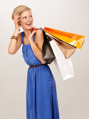 Buy stock photo An attractive young woman holding a bunch of shopping bags