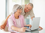 Senior couple using a laptop and a credit card to shop