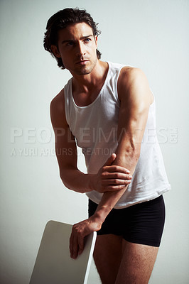 Buy stock photo A handsome young man standing in his vest and underwear