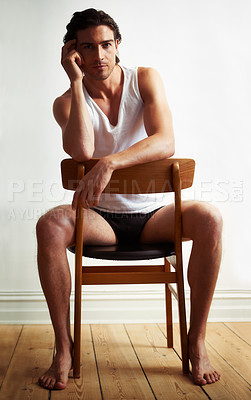 Buy stock photo Portrait of a handsome young man sitting on a chair