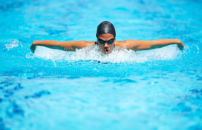Buy stock photo A focused young female swimmer doing the butterfly stroke