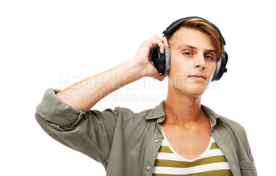 Buy stock photo Studio portrait of a handsome young man listing to music on some headphones isolated on white