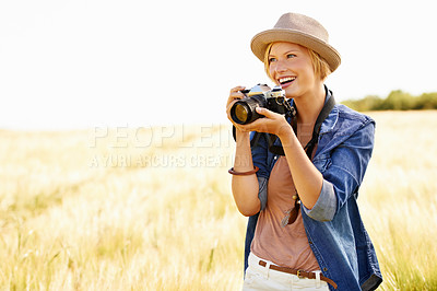Buy stock photo An attractive young woman holding a camera while out in a field
