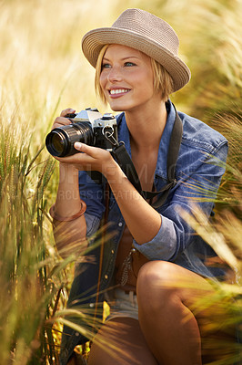 Buy stock photo An attractive young woman holding a camera while crouching in a field