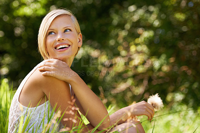 Buy stock photo An attractive young woman sitting in an open field and holding a dandelion