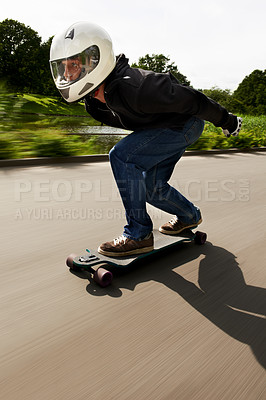Buy stock photo Shot of a man skateboarding down a road on his board