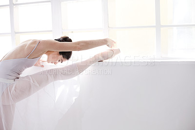 Buy stock photo Supple young ballerina stretching alongside a white wall
