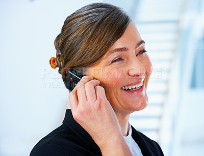 Buy stock photo Talking business over the phone and smiling