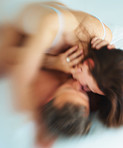 Blur image of a couple lying in bed while kissing